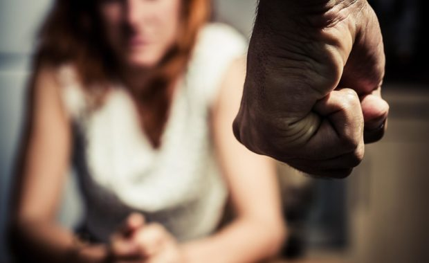 clenched fist in the foreground with victim of domestic in background